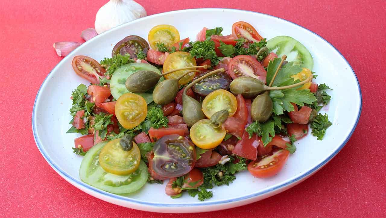 Frische Kräuter und Kapern machen diesen Tomatensalat zu etwas ganz Besonderem